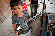 "Sept. 27, 2009 -- TAK BAI, THAILAND: Thai Muslim boys play with toy shotguns in front of their home in Tak Bai, Narathiwat, Thailand. Thailand's three southern most provinces; Yala, Pattani and Narathiwat are often called ""restive"" and a decades long Muslim insurgency has gained traction recently. Nearly 4,000 people have been killed since 2004. The three southern provinces are under emergency control and there are more than 60,000 Thai military, police and paramilitary militia forces trying to keep the peace battling insurgents who favor car bombs and assassination.   Photo by Jack Kurtz"