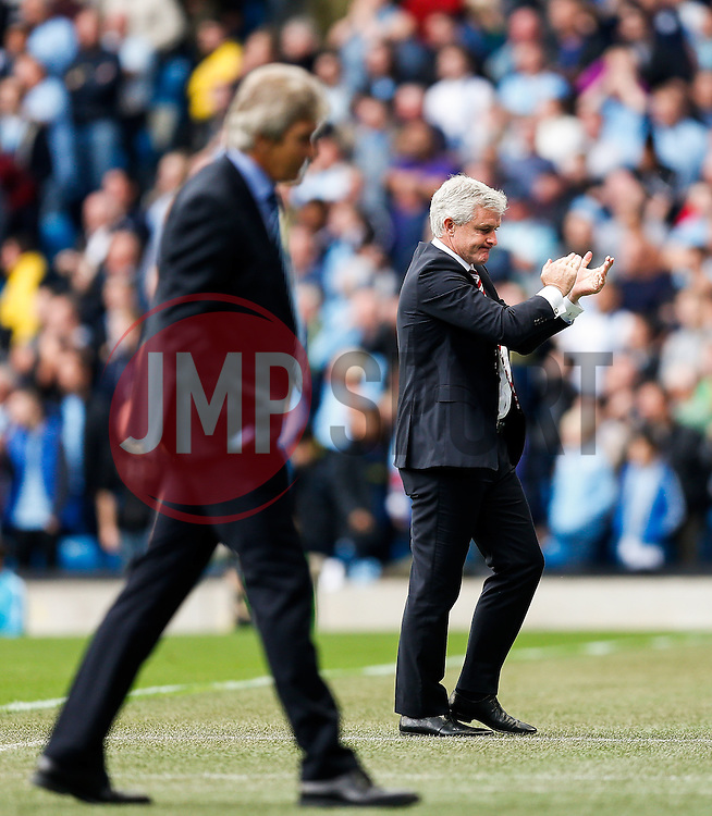 Stoke Manager Mark Hughes celebrates and Manager Manuel Pellegrini of Manchester City looks dejected after Mame Biram Diouf of Stoke scores a goal to give his side a 0-1 lead - Photo mandatory by-line: Rogan Thomson/JMP - 07966 386802 - 30/08/2014 - SPORT - FOOTBALL - Manchester, England - Etihad Stadium - Manchester City v Stoke City - Barclays Premier League.