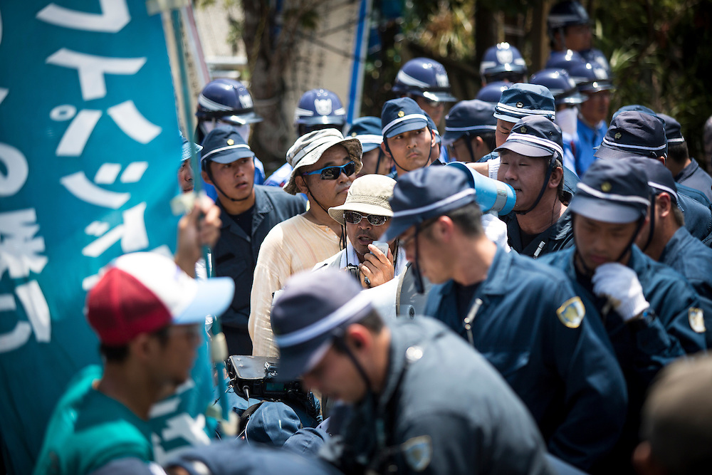 OKINAWA, JAPAN - AUGUST 19 : Anti U.S base leader Hiroji Yamashiro being surrounded by police after staging a sit-in protest protest against the construction of helipads in front of the gate of U.S. military's Northern Training Area in the village of Higashi, Okinawa Prefecture, on August 19, 2016. Japanese government resume construction of total six helipads in a fragile ten million year old Yanbaru forest that is home to endemic endangered species such as the Okinawan rail and Okinawan wood pecker. (Photo by Richard Atrero de Guzman/NURPhoto)