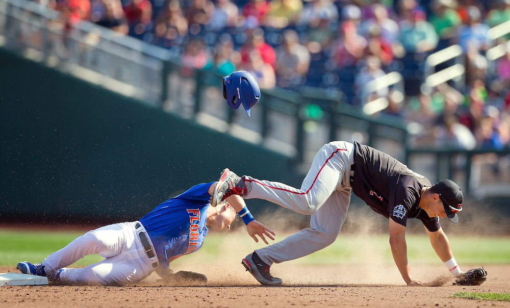 POSTER OPTION. THIS IS UNCROPPED. PLEASE CROP FROM TOP AND ON RIGHT UNTIL IT WORKS. THANKS.<br /> <br /> OMAHA, NEB.  -- 06/21/2016:   Florida's Jonathan India (6), left, collides with Texas Tech's Orlando Garcia (2) as he slides safely into second base in the bottom of the fifth inning during game 7 of the College World Series at TD Ameritrade Park in Omaha, Neb., Tuesday, June 21, 2016.<br /> MATT DIXON/THE WORLD-HERALD