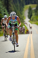 Barbara Fagan, from Milwaukee, Wis., makes the climb up Hayden Lake Road with a pack of several other Ironman competitors.