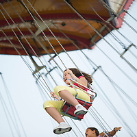 Girl riding the spinning swing at an amusement park