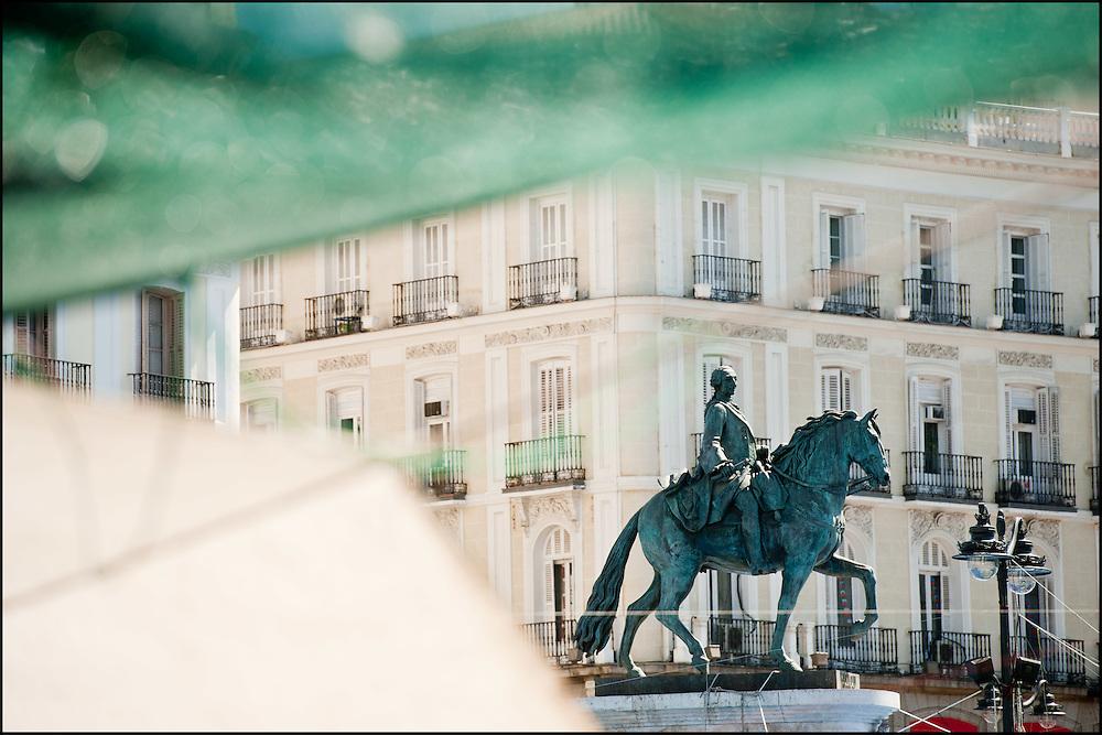 """La statue de Charles III trone au centre du campement place puerta del sol. // Le mouvement spontane du """"15 M"""" (15 mai) compose de citoyens espagnols campe depuis 2 semaines sur la place Puerta Del Sol avec pour revendication la construction d'une democratie nouvelle. Organise en commission les citoyens prennent la parole lors d'assemblee ouverte a tous - Place Puerta Del Sol à Madrid le Juin 2011. ©Benjamin Girette/IP3Press"""