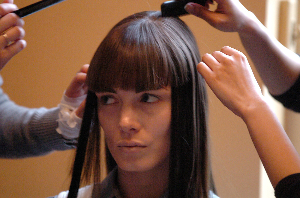 Stylists attend to a models hair before a fashion show at the Royal Academy in London.