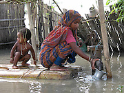zamela khatun, is taking drinking water as because floodwaters inundate her house at chalarkurar village, about 309 kilometers  southwest of Gauhati, capital of northeastern Indian state of Assam, thurshday, July 10, 2003. Floods and mudslides in the northeastern states of Assam and Tripura have killed at least six people over the past week and uprooted more than 500,000 from their homes. (AP Photo/Shib Shankar Chatterjee)