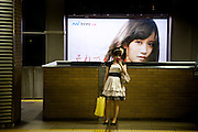TOKYO, JAPAN, 30 SEPTEMBER - Ebisu station - Girl with puffed out dress waiting for the train and playing with her pink mobile. on the background, a commercial portrait -  September 2012