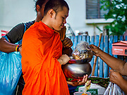 20 JUNE 2018 - BANGKOK, THAILAND:  A person makes merit by giving a Buddhist monk fresh fruit in a plastic bag during the monk's alms rounds at Makkasan Market, a small local market in central Bangkok. Officials in Thailand are wrestling with Thais use of plastic bags. The issue became a public one in early June when a whale in Thai waters died after ingesting 18 pounds of plastic. In a recent report, Ocean Conservancy claimed that Thailand, China, Indonesia, the Philippines, and Vietnam were responsible for as much as 60 percent of the plastic waste in the world's oceans.      PHOTO BY JACK KURTZ