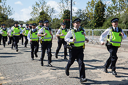 London, UK. 4 September, 2019. Metropolitan Police officers run towards anti-nuclear activists protesting outside ExCel London on the third day of a week-long carnival of resistance against DSEI, the world's largest arms fair. The third day's protests were organised by the Campaign for Nuclear Disarmament (CND) and Trident Ploughshares.