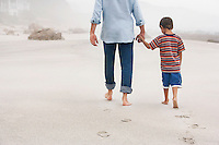 Father and son (5-6) holding hands walking on beach back view