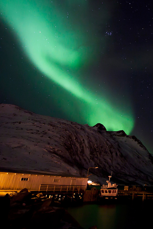 The Aurora Borealis (Northern Lights) at Ersfjordbotn in Tromso, Norway with a small boat named Aurora I in the foreground.