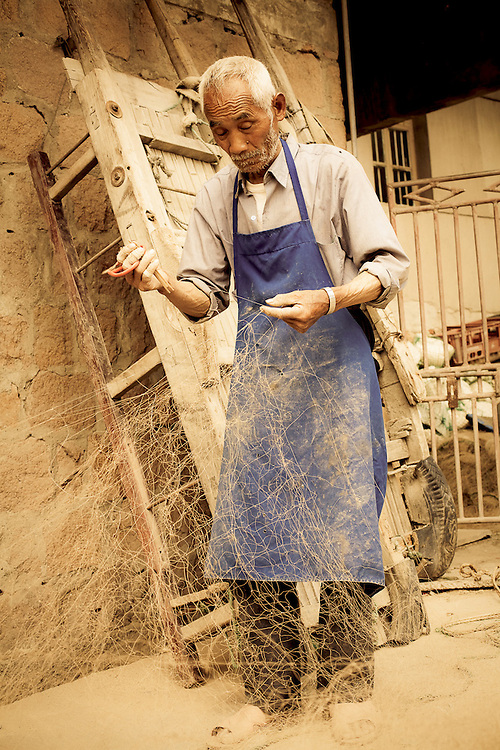 old man mending nets