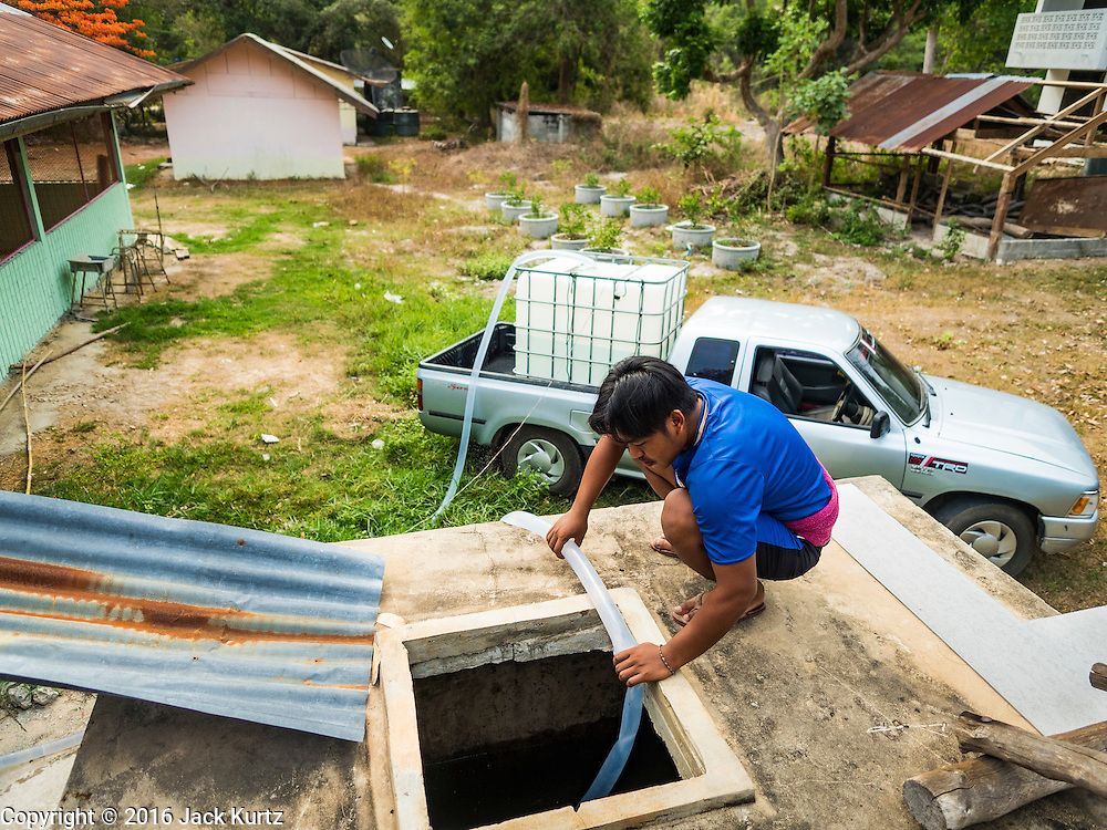 10 MAY 2016 - TA TUM, SURIN, THAILAND:    A man at the public school in Ban Khana fills the water cisterns with water from the artesian well in Ta Tum, Surin, Thailand. The school hasn't had running water for about one month. The well is the most important source of drinking water for thousands of people in the communities surrounding it.  In the past many of the people had domestic water piped to their homes or from wells in their villages but those water sources have dried up because of the drought in Thailand. Thailand is in the midst of its worst drought in more than 50 years. The government has asked farmers to delay planting their rice until the rains start, which is expected to be in June. The drought is expected to cut Thai rice production and limit exports of Thai rice. The drought, caused by a very strong El Nino weather pattern is cutting production in the world's top three rice exporting countries:  India, Thailand and Vietnam. Rice prices in markets in Thailand and neighboring Cambodia are starting to creep up.    PHOTO BY JACK KURTZ