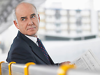 Mature Businessman Sitting on Bench with newspaper looking over shoulder