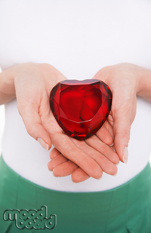 Woman showing heart-shaped jewel mid section