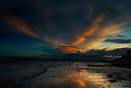 Sunset reflecting on wet sand, Exmouth Beach, Exmouth, Devon, England.