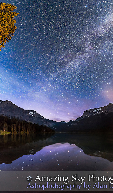 The stars of Cassiopeia (the &ldquo;W&rdquo; at centre) and the other stars of the summer and autumn sky reflected in the still waters of Emerald Lake, in Yoho National Park, BC. Vega is at top, Deneb below it, while the stars of Perseus and Pegasus are just rising. The sky is blue from the glow of perpetual twilight that lights the sky all night at this latitude in June and early July. This was June 6, 2016. High haze fuzzes the stars naturally here. <br /> <br /> This is a vertical panorama of 4 segments, taken with the iPano unit, and with each segment a 30-second exposure at f/2.2 with the Sigma 24mm Art lens and Nikon D750 at ISO 4000. Stitched with Adobe Camera Raw.