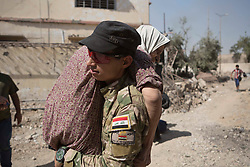 &copy; Licensed to London News Pictures. 15/06/2017. Mosul, Iraq. An Iraqi Army soldier, of 9th Armoured Division, carries a woman to safety as families flee from ISIS held West Mosul.<br /> <br /> Despite heavy fighting between the Islamic State and Iraqi Security Forces many civilians have started to leave ISIS territory in West Mosul. Mosul residents, many of whom have been in hiding in their homes since the start of the West Mosul Offensive, often have to run through ISIS sniper and machine gun fire to reach the safety of Iraqi Security Forces positions. Photo credit: Matt Cetti-Roberts/LNP