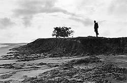 BANGLADESH COX'S BAZAAR DISTRICT MATERBARI JUL94 - A man stands on an eroded embankment on the island of Materbari. Yearly occurrences of hurricanes make this island extremely vulnerable to natural disasters...jre/Photo by Jiri Rezac..© Jiri Rezac 1994