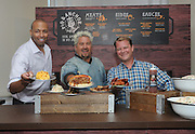 Food Network Star Guy Fieri, center, Malcolm Burn, left, Cruise Director at Carnival Cruise Line, and Eddie Allen, Vice President of Beverage Operations at Carnival Cruise Line, serve up food from Guy Fieri's new Pig & Anchor Bar-B-Que Smokehouse, exclusively on Carnival Cruise Line, Wednesday, July 27, 2016, in New York.  (Diane Bondareff/ AP Images for Carnival Cruise Line)