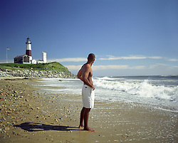 one man alone in shorts standing on the beach in Montauk near the Montauk Lighthouse