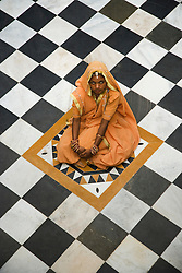 A village girl sitting in the middle of a black and white patterned tile floor,view from above, Jodphur,Rajasthan, India