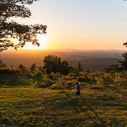 Kids playing in a field on the summit of Mount Agamenticus in York, Maine.