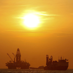 The Transocean Development Driller III works to drill the primary relief well during sunrise at the BP Plc Macondo well site in the Gulf of Mexico off the coast of Louisiana, U.S., on Friday, July 30, 2010. BP Plc continues to work on a relief well to permanently plug the source of the largest oil spill in U.S. history.  Photographer: Derick E. Hingle/Bloomberg