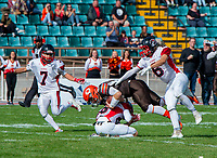 KELOWNA, CANADA - SEPTEMBER 16: Okanagan Sun quarterback Jakob Loucks #2 is tackled during the second quarter by defensive backs Riley Caljouw#26 and Shawn Arabsky #6 of the Vancouver Island Raiders  on September 16, 2018, at the Apple Bowl, in Kelowna, British Columbia, Canada.  (Photo by Marissa Baecker/Shoot the Breeze)  *** Local Caption ***