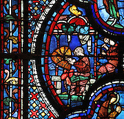 A man decorating a shield, from the donor window of the gunsmiths, from the St John the Evangelist stained glass window, 13th century, in the nave of Chartres cathedral, Eure-et-Loir, France. Unusually, this window is shaped like an axe-head, to reflect its donors' occupation. Chartres cathedral was built 1194-1250 and is a fine example of Gothic architecture. Most of its windows date from 1205-40 although a few earlier 12th century examples are also intact. It was declared a UNESCO World Heritage Site in 1979. Picture by Manuel Cohen