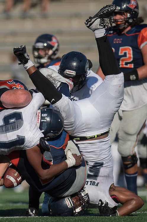 Costa Mesa, CA - Fullerton College defensive lineman Tyler Stepney (58) is upended as he tackles Orange Coast College quaterback Kody Whitaker (3). Fullerton went on to win the team's November 5th, 2016 game 35-14.