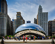 "Tourists surround and are reflected in  ""Cloud Gate"" in Chicago's Millenium Park with Chicago architecture in the background."