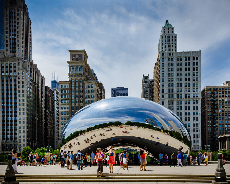 """Tourists surround and are reflected in  """"Cloud Gate"""" in Chicago's Millenium Park with Chicago architecture in the background."""