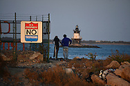 People gaze out at the Orient Point Lighthouse from the very end of a dirt road, the absolute end of Long Island's North Fork in Orient Point.   (Oct. 14, 2012). ©Audrey C. Tiernan
