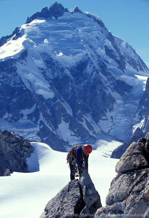 A climber negotiates rock on Claw Peak beneath Mt. Waddington.