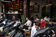 Young Vietnamese in a coffee cafe surrounded by motorcycles in the Old Quarter, Hanoi, Vietnam, Southeast Asia