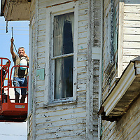David Scruggs, an employee for Wooten Construction, sprays a dish washing mix on the Spain House in Tupelo to rid the home of the wasp infestation on Thursday as the crew works to prep the home for new siding.