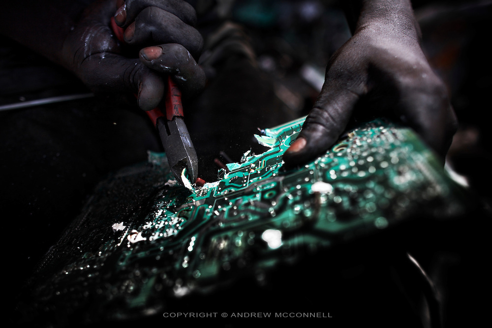 A man rips apart a circuit board to salvage components, at Agbogbloshie dump, in Accra, Ghana.