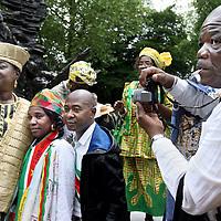 Nederland, Amsterdam , 1 juli 2013.<br /> Afschaffing Slavernij Herdenking in het Oosterpark.<br /> Na afloop van de herdenking zorgt het jaarlijkse Keti Koti festival voor een vrolijkere sfeer. Keti Koti betekent 'Verbroken Ketenen' in het Surinaams, en symboliseert de afschaffing van de slavernij. Het Keti Koti Festival viert jaarlijks vrijheid, gelijkheid en verbondenheid met een kleurrijke explosie van vreugde in het Oosterpark. Op vier podia zijn multiculturele muziek- en dansoptredens en in het hele park kan men genieten van traditioneel eten en drinken, lezingen, films, een Caribische markt en kunst.<br /> Op de foto: winti- priesteres Marian Markelo (l) wordt begroet en vereerd door Surinaamse dames en heren en gaat op de foto.<br /> <br /> <br /> <br /> Foto:Jean-Pierre Jans