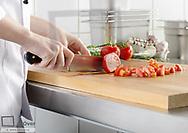 Tomate wird auf Schneidebrett geschnitten (model-released)