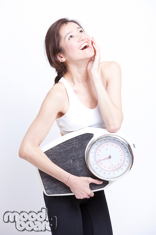Cheerful Asian woman with weight scale against white background