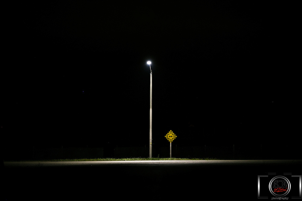 A lone street lamp at the end of a road, in the middle of the night.