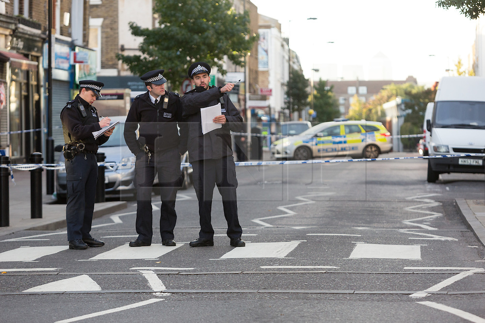 © Licensed to London News Pictures. 27/09/2015. London, UK. Police officers and a police car at the cordon on Chatsworth Road. Police have launched a murder investigation after a man was shot dead in the street outside Regal Pharmacy next to Mighty Meats butcher shop in Chatsworth Road, Hackney, east London yesterday. Photo credit : Vickie Flores/LNP