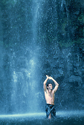 Man in a waterfall in Hawaii