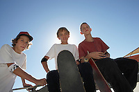 Three teenage boys (16-17) with skateboards outdoors portrait