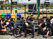 29 OCTOBER 2016 - BANGKOK, THAILAND: Men sleep on Sanam Luang while they wait to go into the Grand Palace to pay homage to the late King. Saturday was the first day Thais could pay homage to the funeral urn of the late Bhumibol Adulyadej, King of Thailand, at Dusit Maha Prasart Throne Hall in the Grand Palace. The Palace said 10,000 people per day would be issued free tickerts to enter the Throne Hall but by late Saturday morning more than 100,000 people were in line and the palace scrapped plans to require mourners to get the free tickets. Traditionally, Thai Kings lay in state in their urns, but King Bhumibol Adulyadej is breaking with tradition. His urn reportedly contains some of his hair, but the King is in a coffin,  not in the urn. The laying in state will continue until at least January 2017 but may be extended.      PHOTO BY JACK KURTZ