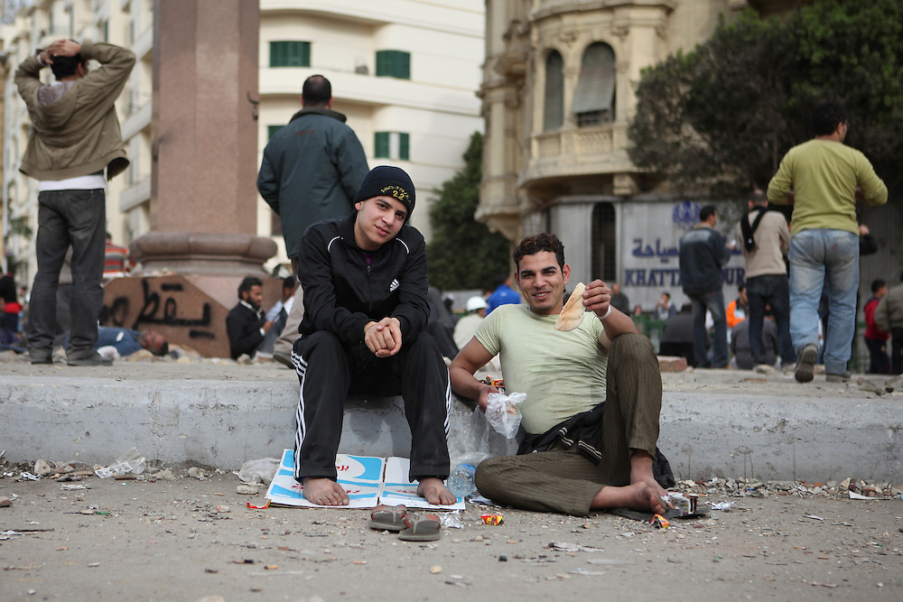 Two protesters who were involved with clashes against Mubarak's thugs enjoy sandwiches at a site near Tahrir Square.