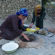 Women baking bread in an outdoor stone oven in the early morning, Nokhur village, Turkmenistan