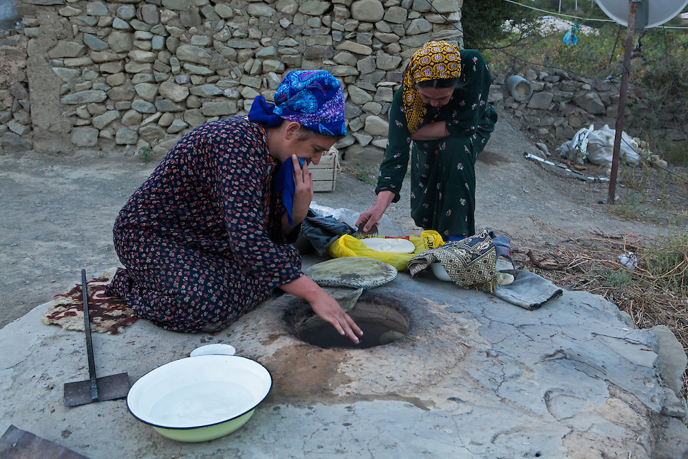 Women baking bread in an outdoor stone oven in the early morning, Nokhur village, Turkmenistan