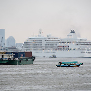 A large passenger cruise ship with other smaller ships in the foreground on the Saigon River in Ho Chi Minh City, Vietnam.