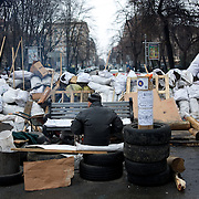 December 19, 2013 - Kiev, Ukraine: A Pro-EU demonstrator sits beside a barricade on a road leading to Independence Square.<br /> On the night of 21 November 2013, a wave of demonstrations and civil unrest began in Ukraine, when spontaneous protests erupted in the capital of Kiev as a response to the government's suspension of the preparations for signing an association and free trade agreement with the European Union. Anti-government protesters occupied Independence Square, also known as Maidan, demanding the resignation of President Viktor Yanukovych and accusing him of refusing the planned trade and political pact with the EU in favor of closer ties with Russia.<br /> After a days of demonstrations, an increasing number of people joined the protests. As a responses to a police crackdown on November 30, half a million people took the square. The protests are ongoing despite a heavy police presence in the city, regular sub-zero temperatures, and snow. (Paulo Nunes dos Santos/Polaris)